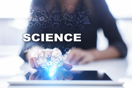 equation: Woman is using tablet pc, pressing on virtual screen and selecting science. Stock Photo