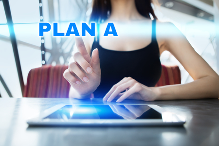 Woman is using tablet pc, pressing on virtual screen and selecting plan a. Stock Photo