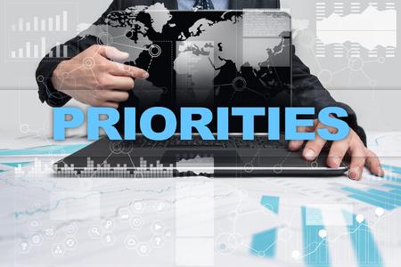 priorities: Businessman presenting priorities concept. Stock Photo