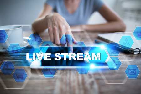 live stream radio: Woman using tablet pc, pressing on virtual screen and selecting live stream. Stock Photo