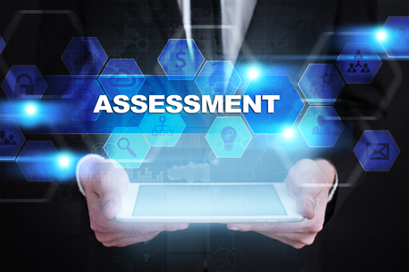 assessments: Businessman holding tablet PC with assessment concept.