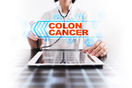 Medical doctor using tablet PC with colon cancer medical concept.