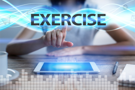 Woman using tablet pc, pressing on virtual screen and selecting exercise. Stock Photo
