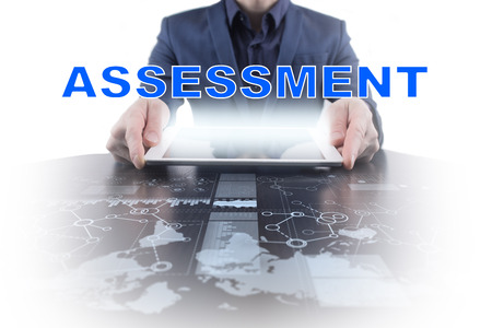 assessments: Businessman working with modern tablet PC and presenting assessment concept.