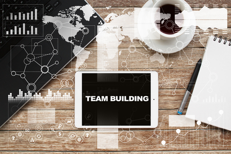 Tablet on desktop with team building text.