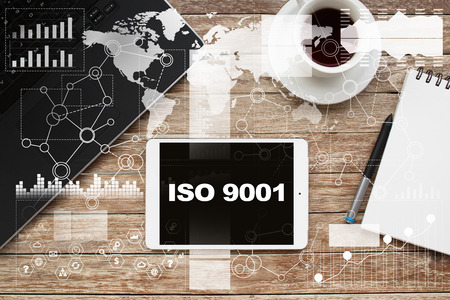 Tablet on desktop with iso 9001 text. Banco de Imagens