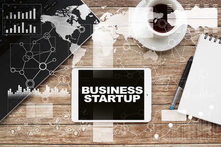 investor: Tablet on desktop with business startup text. Stock Photo