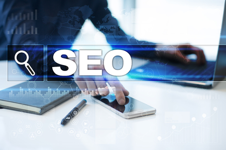 Businessman working in office, pressing button on virtual screen and selecting seo.