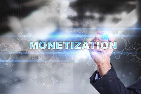 Businessman drawing on virtual screen. monetization concept.