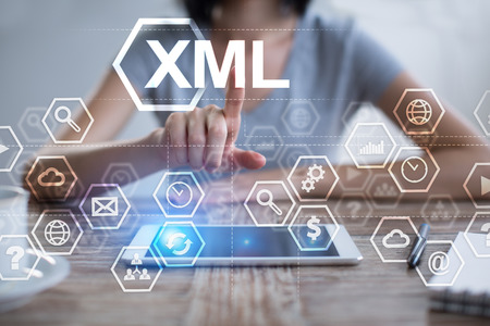 xml: Woman using tablet pc, pressing on virtual screen and selecting xml. Stock Photo