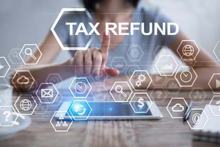 Woman using tablet pc, pressing on virtual screen and selecting tax refund.