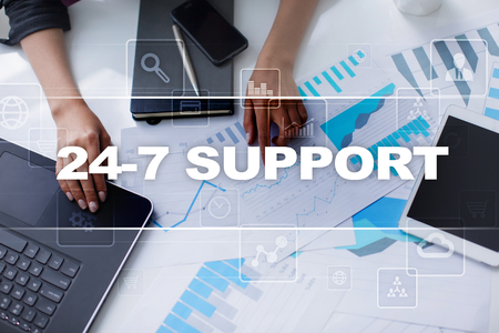 24x7: Woman working with documents, tablet pc and notebook and selecting 24-7 support.