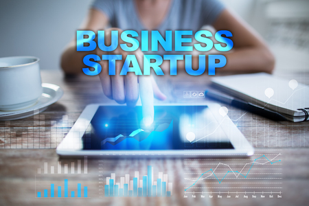Woman using tablet pc, pressing on virtual screen and selecting business startup. Stock Photo