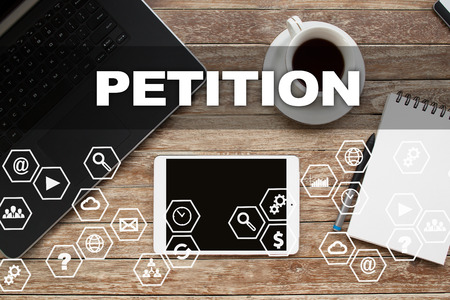 Tablet on desktop with petition text.