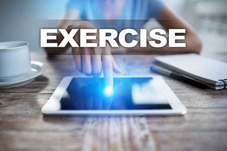 using tablet: Woman using tablet pc, pressing on virtual screen and selecting exercise. Stock Photo