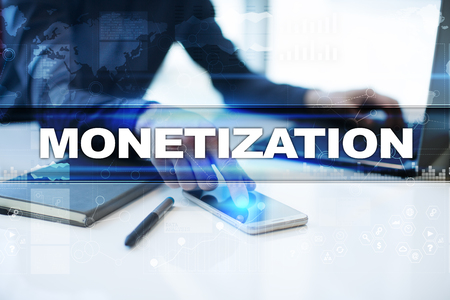 Businessman working in office, pressing button on virtual screen and selecting monetization.
