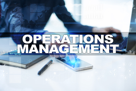 Businessman working in office, pressing button on virtual screen and selecting operations management.