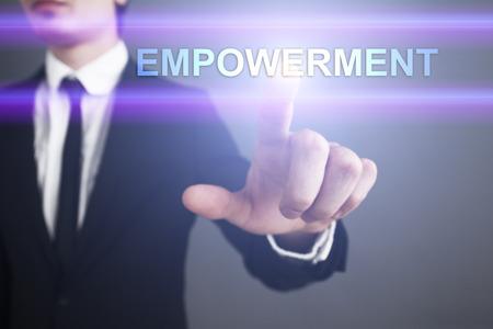 enabling: Businessman selecting empowerment on virtual screen. Stock Photo