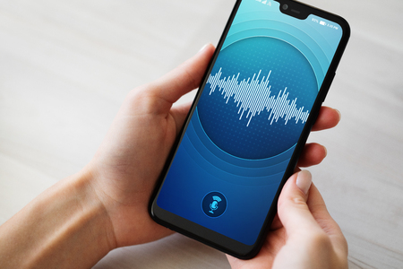 Voice recognition application on smartphone screen. Artificial intelligence and deep learning concept