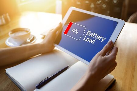 Battery low message on mobile device screen. Internet and technology concept.