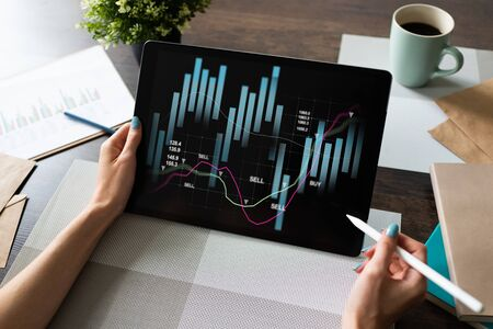 Financial graphs on device screen. Online Investment and stock trading concept. Stock Photo