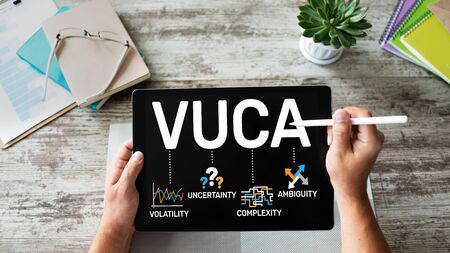 Hand writing on screen with VUCA world concept