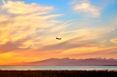 Sunset. Sunset Sky. A plane is attempting to climb in the sunset sky. Stock Photo
