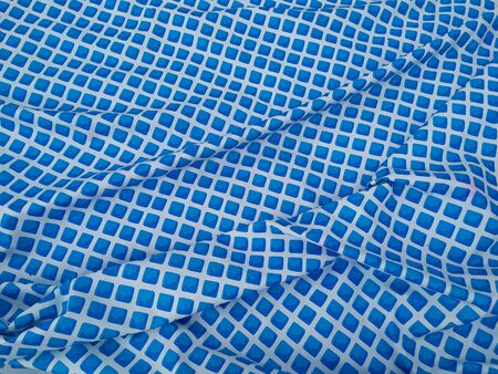 Reflective water surface of a swimming pool, tiles with blue mosaic, giving a blurred impression. Banco de Imagens