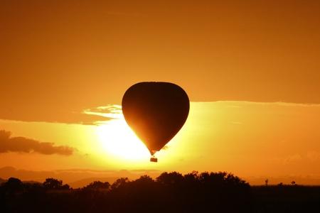 Hot air balloon flying at sunrise over Masai Mara Park, Kenya