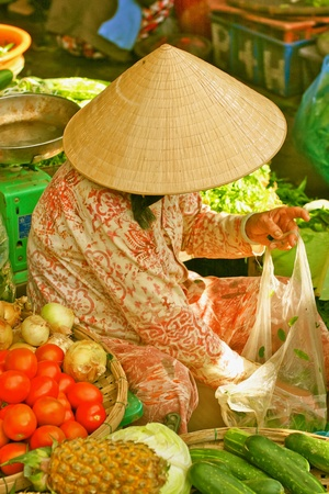 Vietnamese woman selling vegetables on the market street, Hanoi, Vietnam