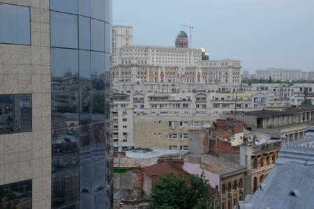 Overview of a variety of contrasting architectural styles of buildings in Bucharest, a capital of Romania. With the modern glass building reflecting old, classical and modern ones.