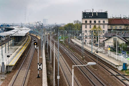 KRAKOW, POLAND-APRIL 12, 2019: Top view of the empty Krakow Podgorze transit stop and train station with platform, tracks, railways; industrial constructions in the background. Cityscape and architecture.