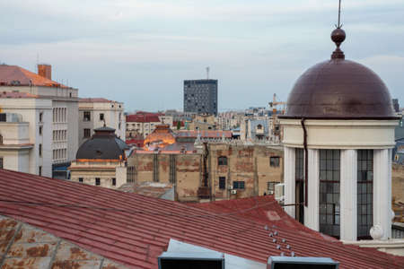 Bucharest, Romania: JUNE 11-2019: Eclectic downtown rooftops seen from the roof with the romanesque dome or top dominating and new modern building in distance. Architecture and cityscape.