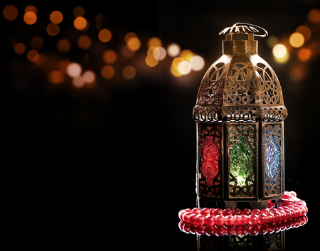 Vintage lantern with red rosary. Ramadan mood at night with light decoration in the background. Stok Fotoğraf