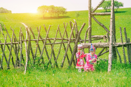 Mother and daughter wearing Mongolian costumes on the grassland