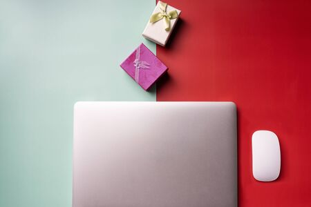 Tablet and gift boxes on red green background