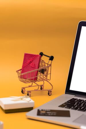Bank card and laptop, shopping cart with gifts on yellow background