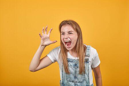 Jeune femme portant un t-shirt blanc, sur fond orange montre des émotions
