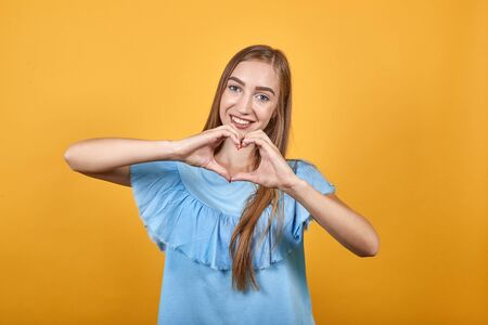 girl brunette in blue t-shirt over isolated orange background shows emotions