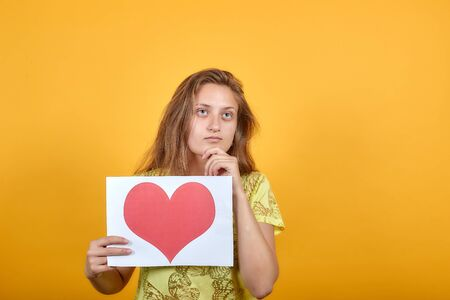 brunette girl in yellow t-shirt over isolated orange background shows emotions