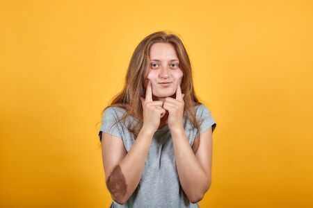 brunette girl in gray t-shirt over isolated orange background shows emotions Stock fotó