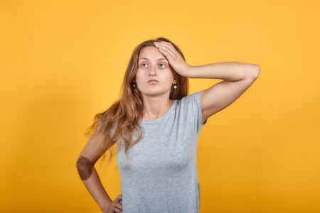 brunette girl in gray t-shirt over isolated orange background shows emotions 写真素材