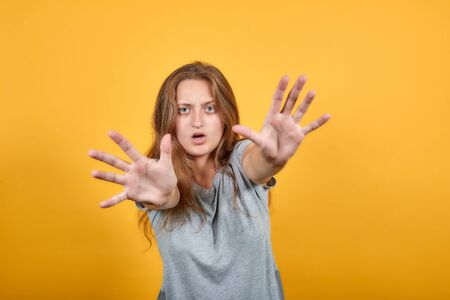 brunette girl in gray t-shirt over isolated orange background shows emotions Stock Photo
