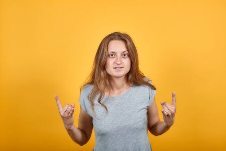 brunette girl in gray t-shirt over isolated orange background shows emotions Фото со стока