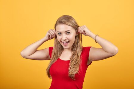 young blonde girl in red t-shirt over isolated orange background shows emotions Stock fotó