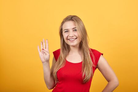 young blonde girl in red t-shirt over isolated orange background shows emotions 免版税图像