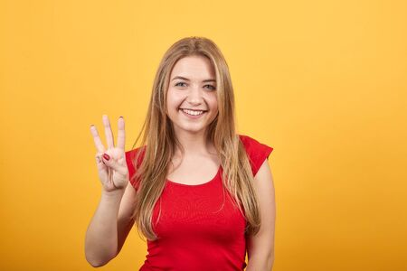 young blonde girl in red t-shirt over isolated orange background shows emotions Stockfoto
