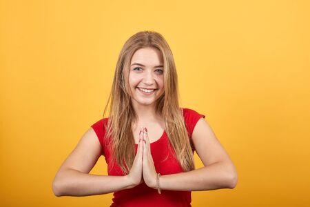 young blonde girl in red t-shirt over isolated orange background shows emotions Archivio Fotografico