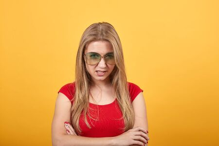 young blonde girl in red t-shirt over isolated orange background shows emotions Фото со стока