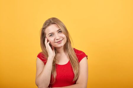 young blonde girl in red t-shirt over isolated orange background shows emotions Banco de Imagens - 132105467